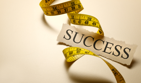 measuring tape wrapped around the word success