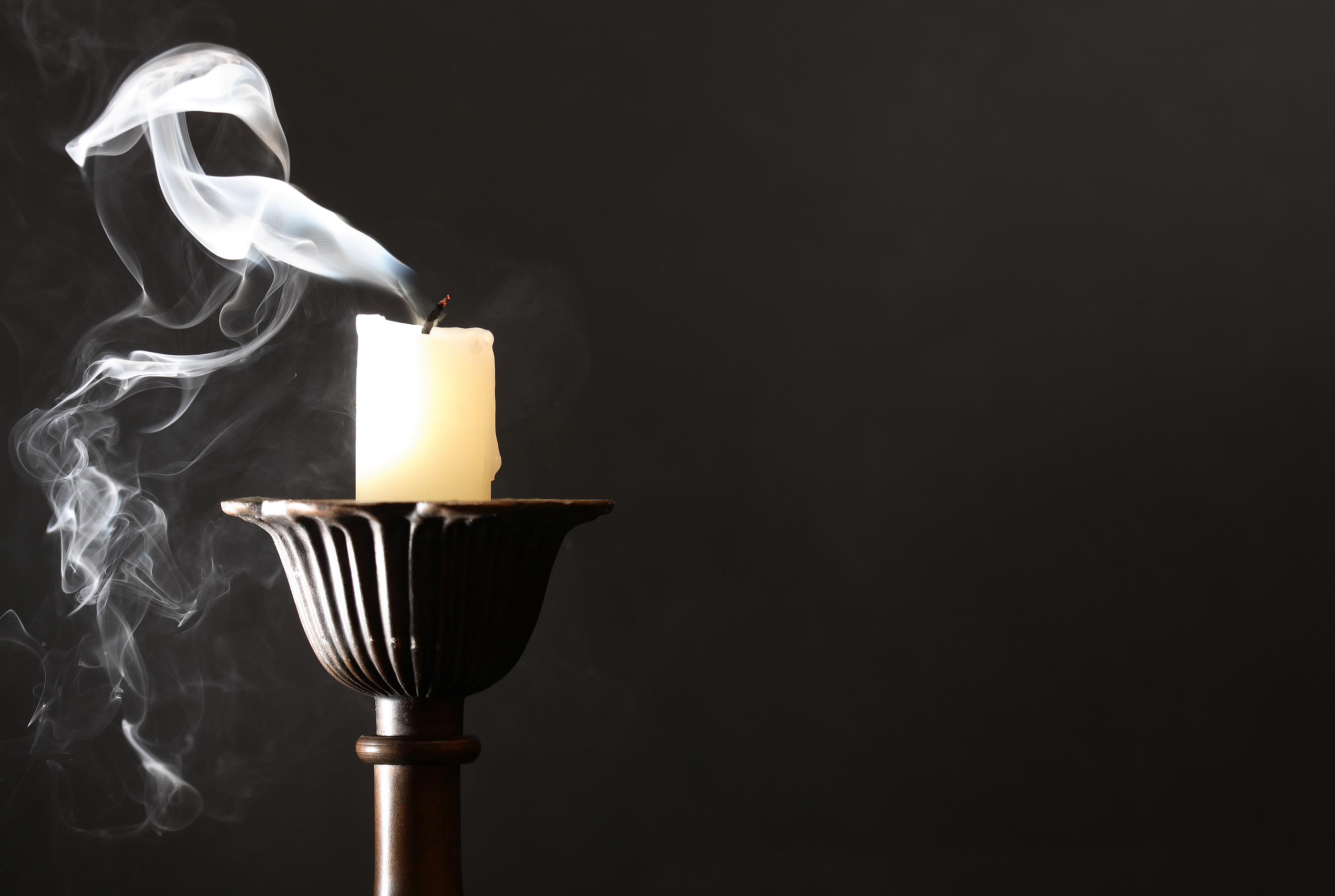 Extinguished candle in candlestick with smoke on dark background